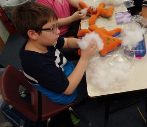 Northwest Elementary student working hard to stuff his second bear!